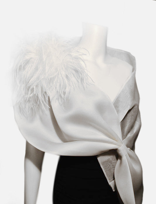 """This elegant evening wrap (Style OSO) measures 63""x 15"" . It is made of satin organza and metallic silk organza with pleating detail and ostrich feathers at the shoulder. It is adjustable via a loop closure and fits most, but can be customized to fit larger sizes. Available in white or cream, this eye catching wrap will turn your dress into a couture outfit."
