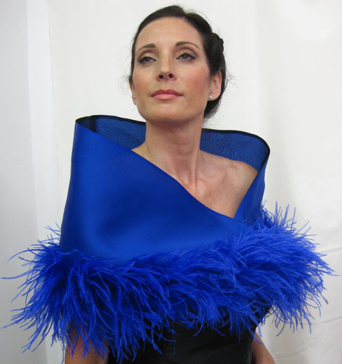 "This is a 100% silk evening wrap made of satin faced organza and lined with silk organza. It features ostrich feathers at the border, a tie closure and measures 49"" x 13' but can be customized for larger sizes. Available in several colors, it is a bold, dramatic statement piece for your special occasion."