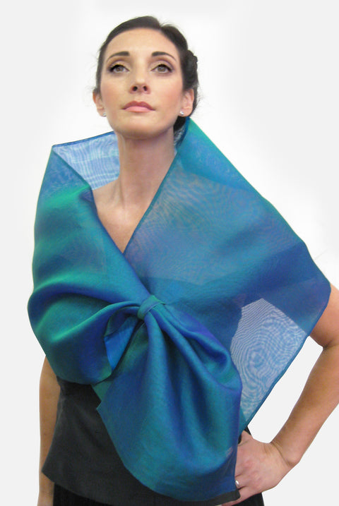 A blue silk organza wrap with a loop closure for easy adjustment and may be worn as a wrap or scarf.  Simple, elegant and dramatic, it creates different looks by pulling the piece through the loop.