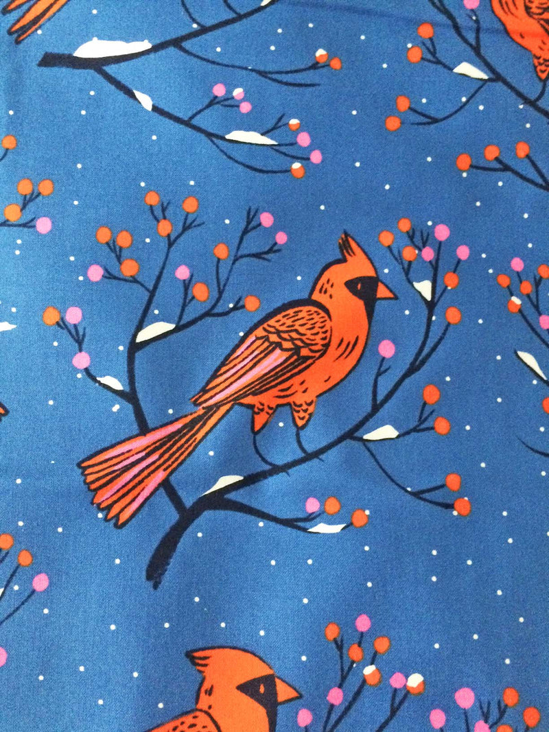 Big red cardinals sit on berry branches on bright rich blue cotton fabric - view 1
