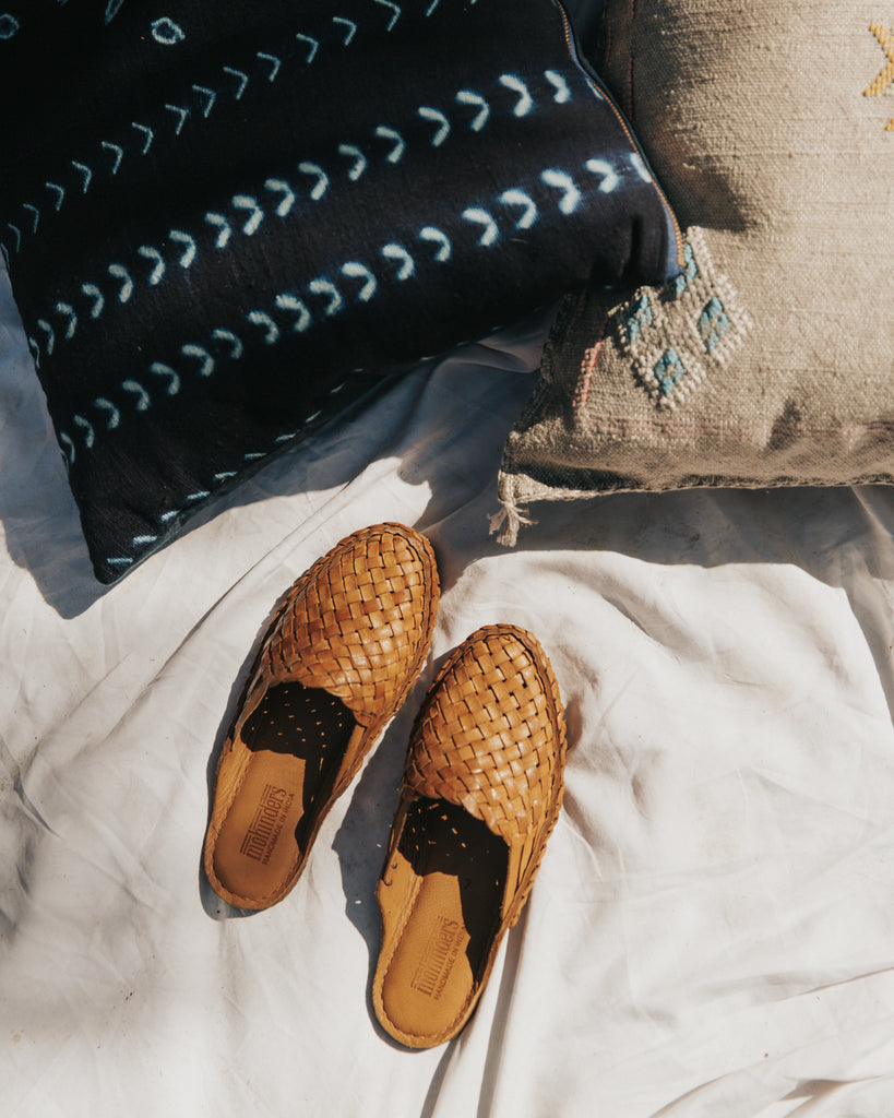 Mohinders slides made ethically in India and shown with handmade bogolan mudcloth pillows made by Thread Spun