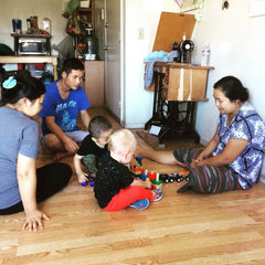 Former refugees living in San Diego play with American-born boy, son of Thread Spun founders.