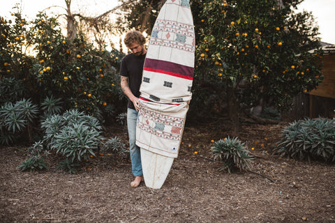 A custom handmade surfboard bag is held by a man. The surfboard bag uses colorful textiles from around the world that are handmade in an ethical environment