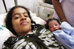 A new mother and her baby helped by Circle of Health International, a nonprofit partner of social enterprise Thread Spun, which makes handmade surfboard bags.