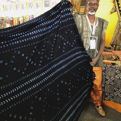 Thread Spun fair trade artisan from Burkina Faso showing off his naturally and hand-dyed, handmade textiles for sale.