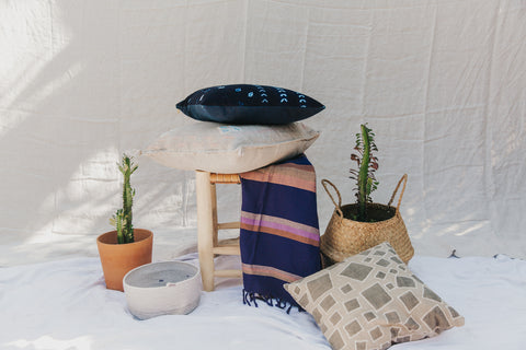 Thread Spun handmade pillows with fair trade and handwoven textiles sit with other fair trade home goods including planters and pots