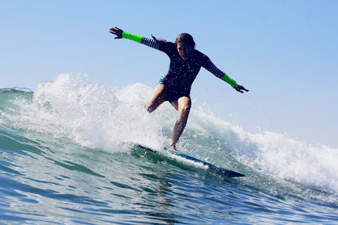 Mom blogger Devon DeMint surfs a wave in Encinitas, California.