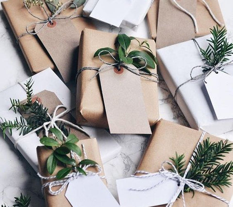 Gifts wrapped in eco-friendly packaging for the holidays utilize brown paper, twine and natural greenery