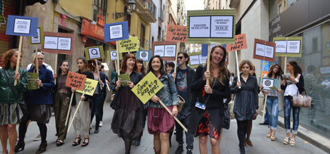 "People from around the world hold signs that state ""Who made my clothes?"" in support of Fashion Revolution"