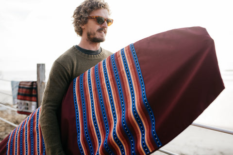 A man holds his surfboard and Thread Spun handmade surfboard bag featuring eco-friendly fabrics at Beacons Beach in Leucadia, California
