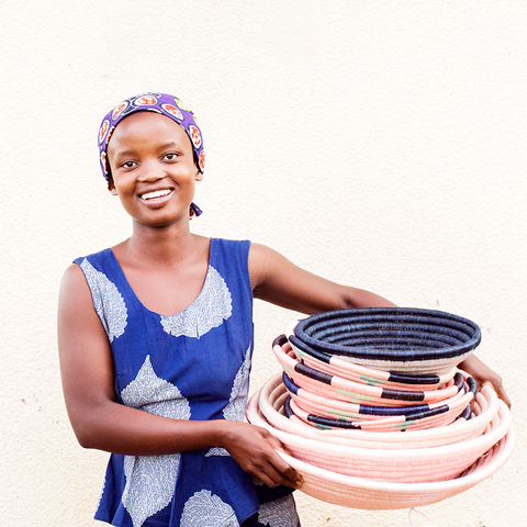 Woman artisan holds a stack of baskets she weaved for Indego Africa, sold by Thread Spun in their Encinitas boutique