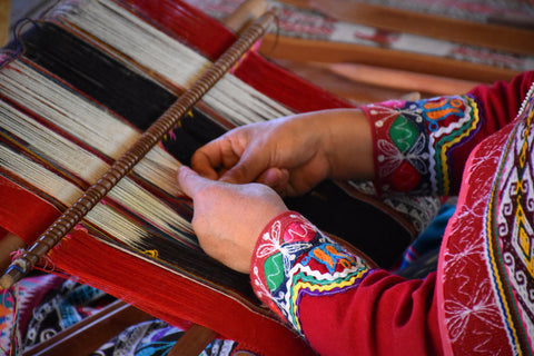 An artisan woman weaving by hand in her community