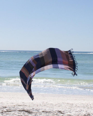 A handwoven Turkish style towel at the beach is handmade by Minna and sold by Thread Spun