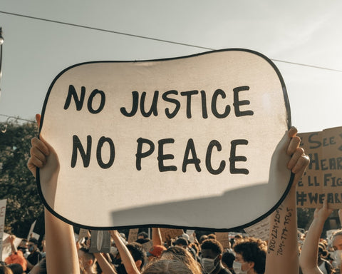 Sign reading No Justice No Peace at a demonstration in the United States for racial equality