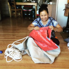 A refugee originally from Burma and now living in San Diego is employed by Thread Spun. She sews surfboared bags by hand using textiles hand woven by artisans from around the world.