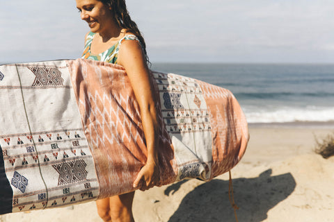 A surfer at the beach holds her surfboard and custom handmade surfboard bag in colorful textiles from Guatemala made by Thread Spun