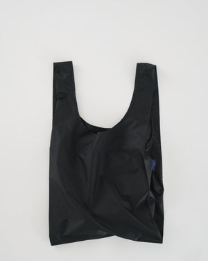 Standard Baggu reusable bag in black. A reusable bag that's not just for the grocery store, it goes everywhere and hauls (practically) anything. Carry in your hand or over your shoulder. Holds 2-3 plastic grocery bags worth of stuff.