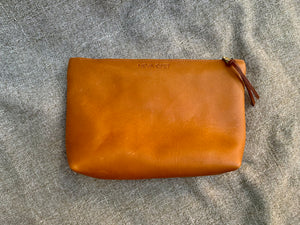 Handmade leather clutch. Made in Atlanta with sustainability in mind. This oil hide clutch has been hand cut from a soft yet sturdy 5 oz. oil hide leather with an attached hand strap for extra security during an evening out.