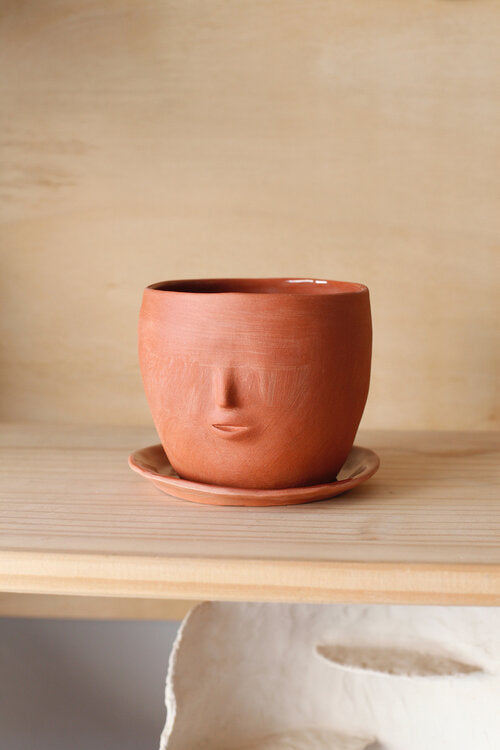 Handmade terracotta face pot with a drainage hole and dish to catch water. Made by artist Rami Kim in Los Angeles.
