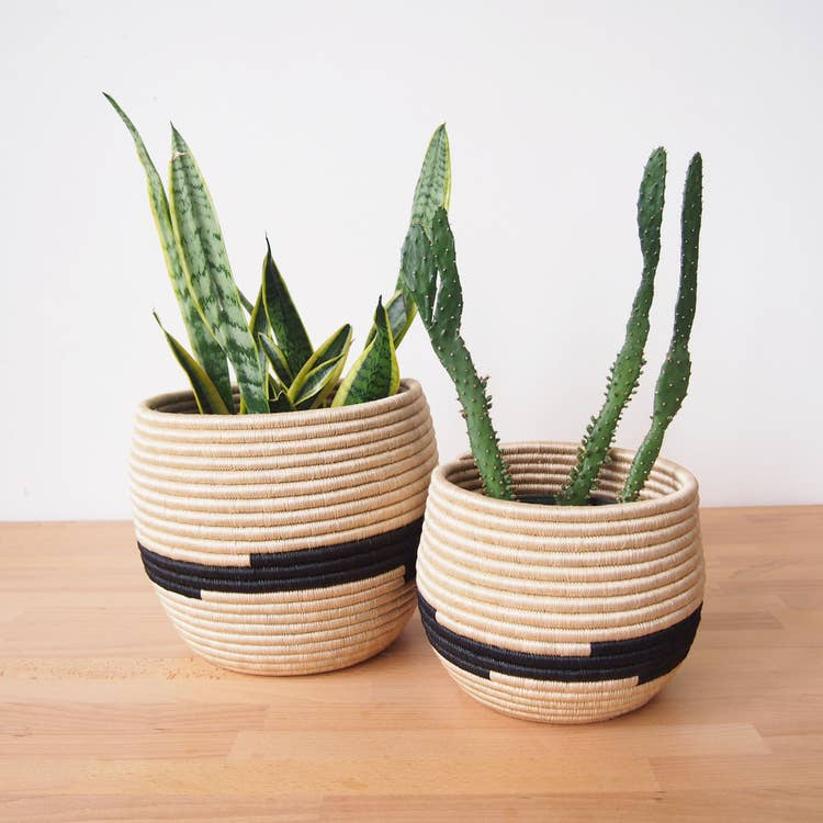 Handmade, woven basket planters made by artisans in Gitarama, Rwanda. The women hand-dye and weave the fibers into these beautiful works of art. The sisal is woven around sweetgrass, a fragrant grass with a subtle sweetness. Use these African baskets as a desk accessory, a plant holder, or to brighten up a shelf.