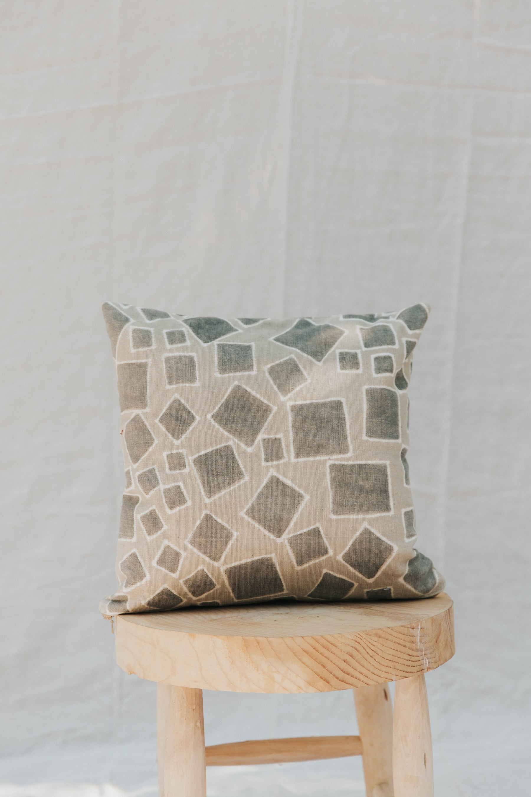 This handmade pillow features a naturally-dyed and fair trade textile from Mali. It is sewn by a resettled refugee paid above a living wage in San Diego, California. The cooperative of artisans that created this textile hires and trains underemployed and educated youth.