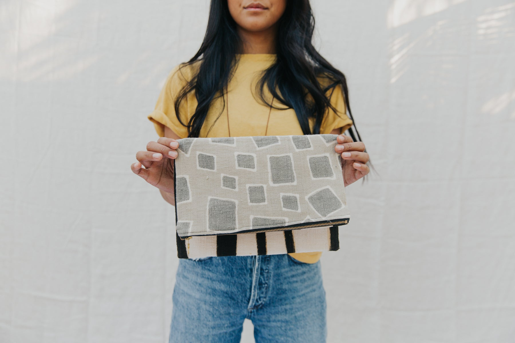 Handmade foldover/reversible clutch featuring fair trade textiles naturally-dyed by artisans from Mali. Each clutch is lined with 100% organic cotton. Sewn by our resettled refugee artisan, Lashta, locally in San Diego.