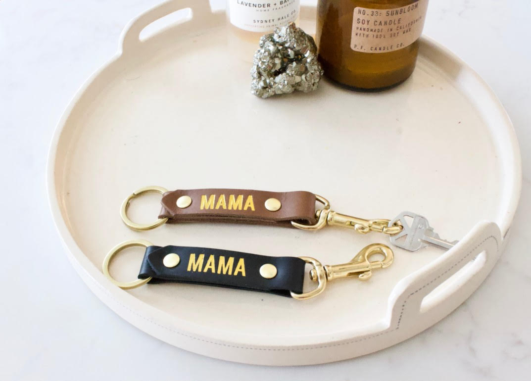 "Handmade leather key fobs or keychains reading ""MAMA"". A Thread Spun collaboration with our favorite leather makers at Neva Opet in Atlanta. A classic leather key fob keychain with solid brass hardware. Choose from brown or black leather with gold emboss reading ""MAMA""."