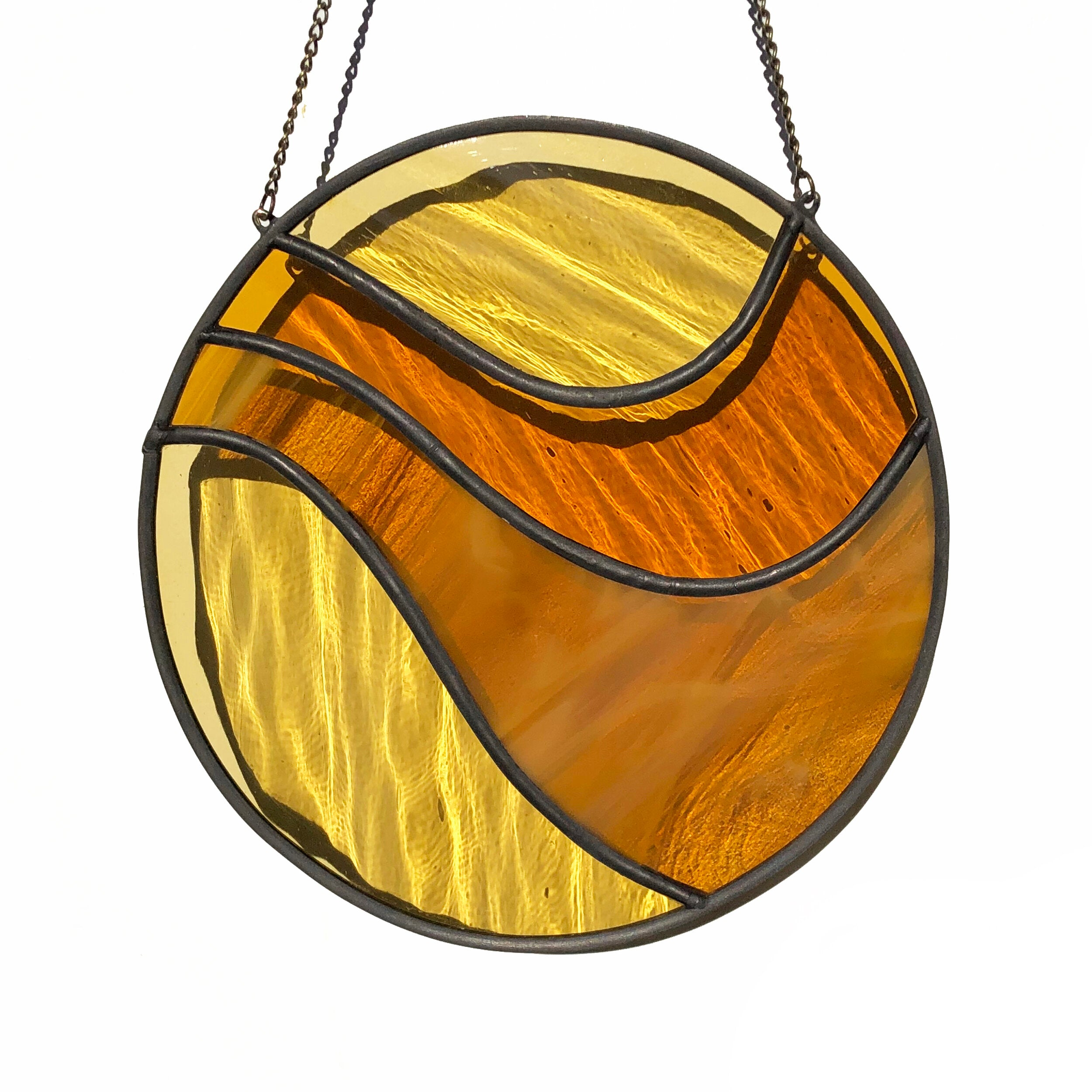 "Handmade stained glass wall or window hanging. Groovy. Measures 3.5"" x 3.5"" not including chain. Arrives ready to hang. Chain measures 8"". Available in shades of ochre and rust or blues."