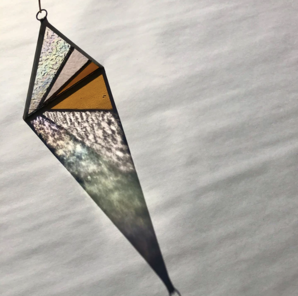 Handmade stained glass triangle by Debbie Bean. Original lead stained glass diamond carefully made out of individually cut textured colored stained glass. Due to the nature of the glass used in creating these triangles, when hung in a sunny place or near a light source, they create colorful shadows.