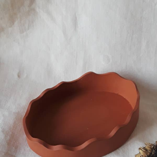 "Handmade, matte terracotta color wavy dish. Perfect for burning incense, for use as a jewelry dish and more. Left unglazed for a matte finish. Handmade in Philadelphia, Pennsylvania. This oval shaped dish measures 6"" x 4"" by 1.5""."