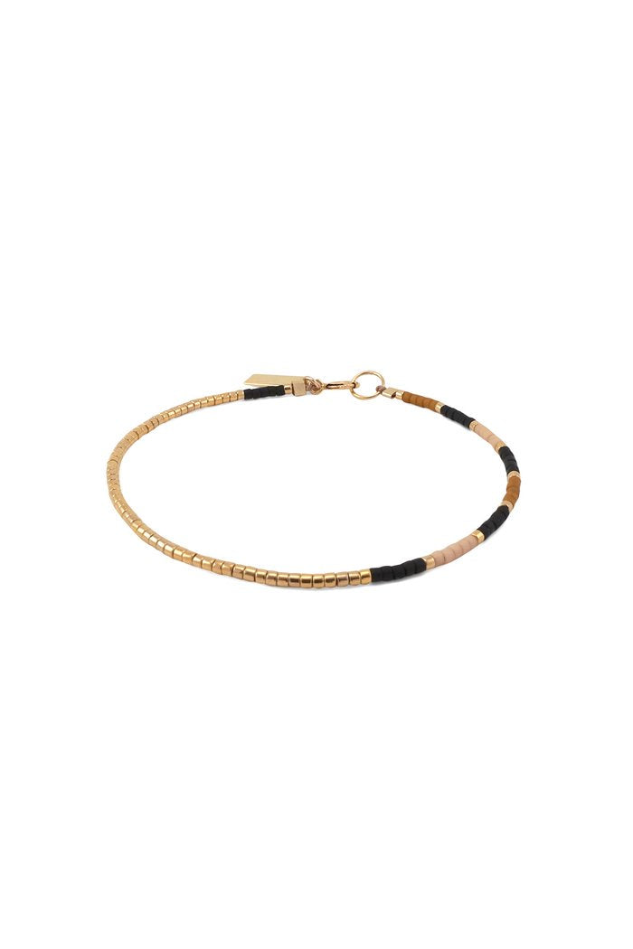 An asymmetrical, beaded bracelet made with glass and silver galvanized glass beads on silk cord. Features a design with a pattern of alternating palette colors that transitions into a long gold segment. Rich, earthy ochre, matte black, and warm blush accented with gold.