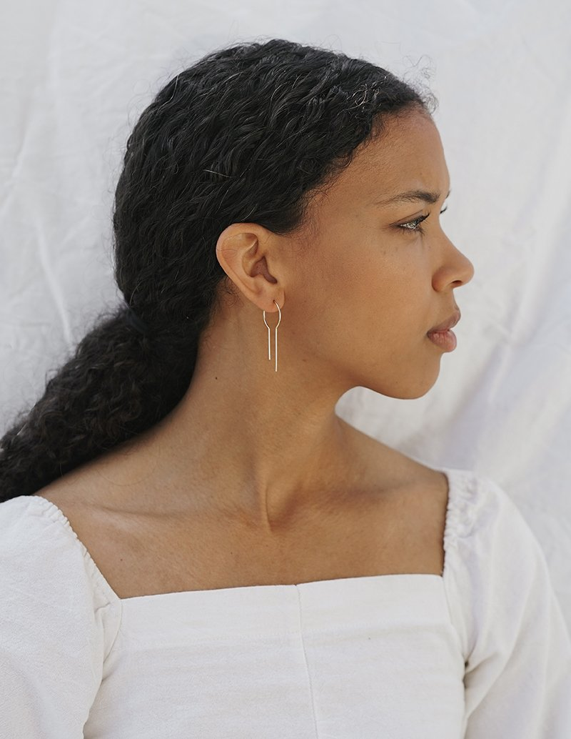 Earrings made from gold-filled wire and hand-formed, they simply thread through the ear for easy wearability and multiple wearing options, made in Seattle, WA by sustainable jewelry brand Baleen