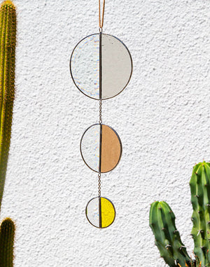 Handmade stained glass wall hanging in the shape of a sun totem. When positioned next to an opened window it will catch the refreshing outdoor breeze and dapple vivid color and - thanks to the semi-circle bevel - rainbows across your space.