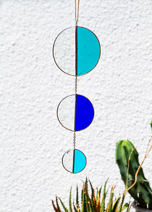 Open image in slideshow, Handmade stained glass wall hanging in the shape of a sun totem. When positioned next to an opened window it will catch the refreshing outdoor breeze and dapple vivid color and - thanks to the semi-circle bevel - rainbows across your space.