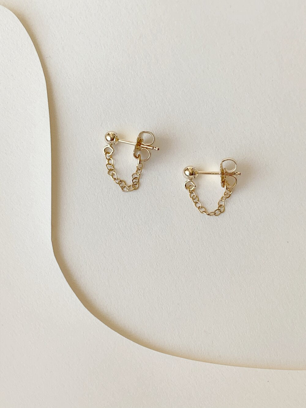 Tiny ball studs and delicate gold chain to wrap your earlobes. Handmade in Los Angeles.