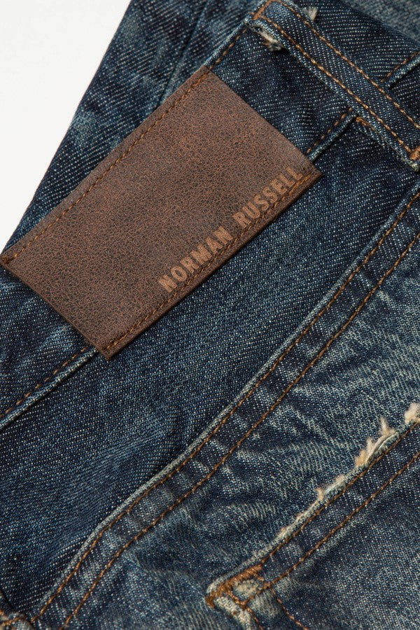 Detail of the leather Norman Russell brand tag on the back of the Cookie dark denim jeans