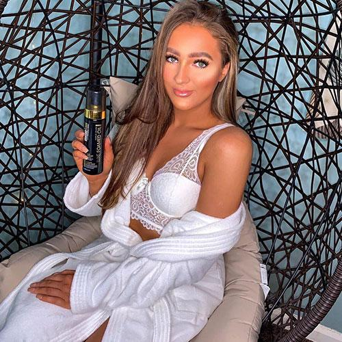 tanned woman sitting down with luxe foamed oil self tan in hand