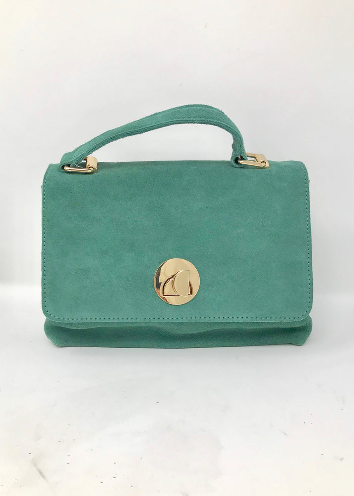 Sage handbag with handle on the top, flap closure with metal hardware, an inside zipper closure.
