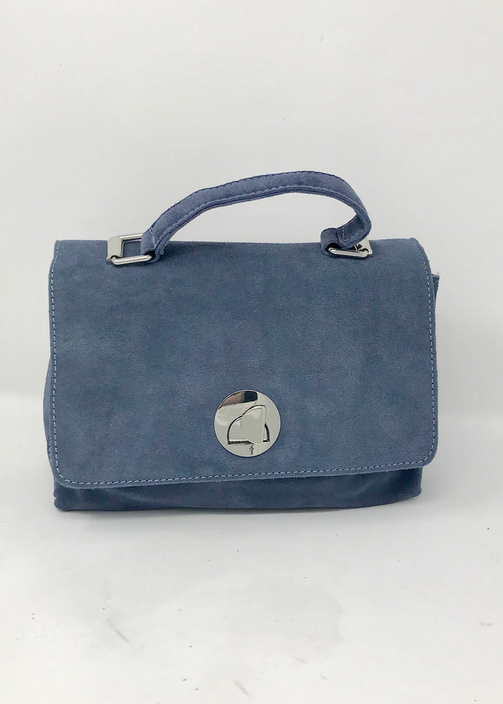 Denim handbag with handle on the top, flap closure with metal hardware, an inside zipper closure