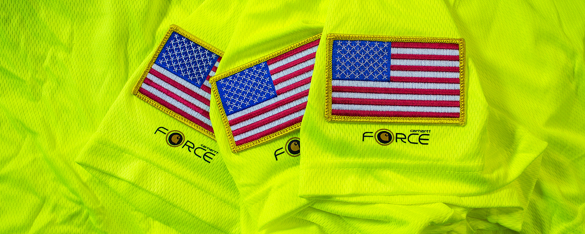 Professional embroidery examples of American flag patches sewn onto Carharrt safety green performance shirts at Strange Planet Printing in Brockton, MA