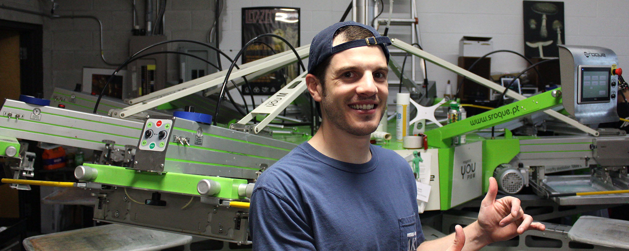 Justin Mantell is the screen printing production manager at Strange Planet Printing pictured standing in front of an 8 color automatic screen printing press made by SRoque.