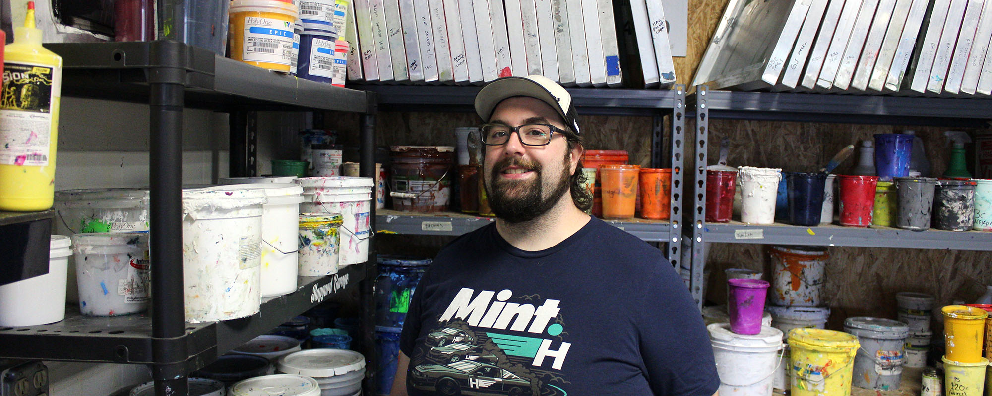 Jeff Clarke of Strange Planet Printing standing in front of a wall of screens and custom mixed Pantone inks for screen printing.