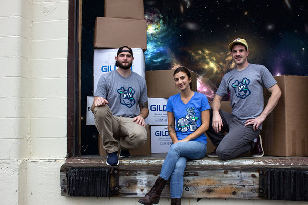 picture shows three owners of strange planet printing sitting on the loading dock to promote free ups ground shipping within the USA