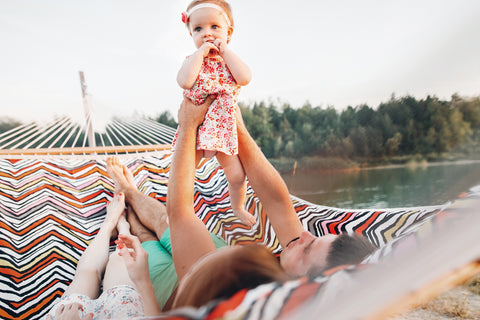 Couple laying in hammock with baby