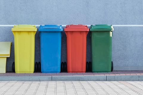 Multi colour trash bins lined up beside building