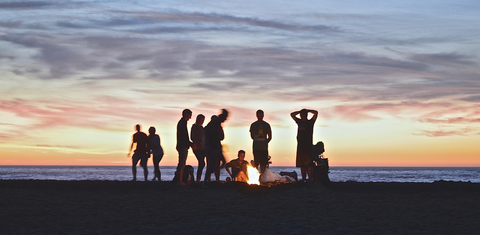 People standing around campfire on beach