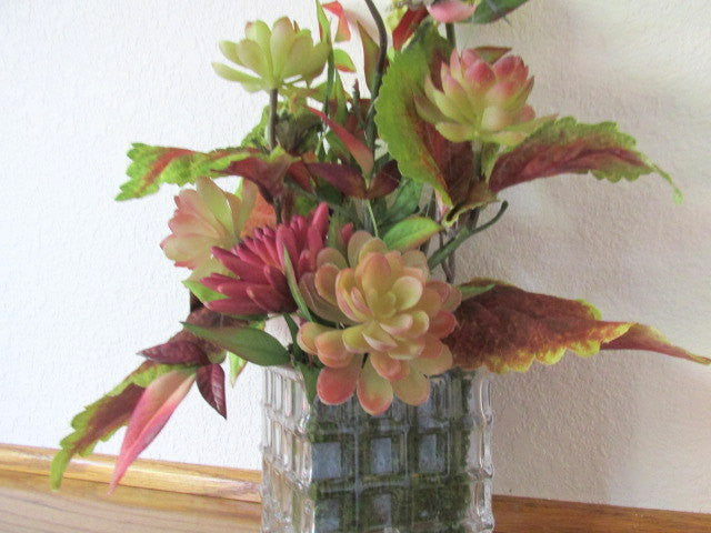 Arrangement with Hummingbird, Succulents and and Silk Leaf Accents in Green and Rose Burgundy with Clear Geometric Glass Container - Odyssey Creations