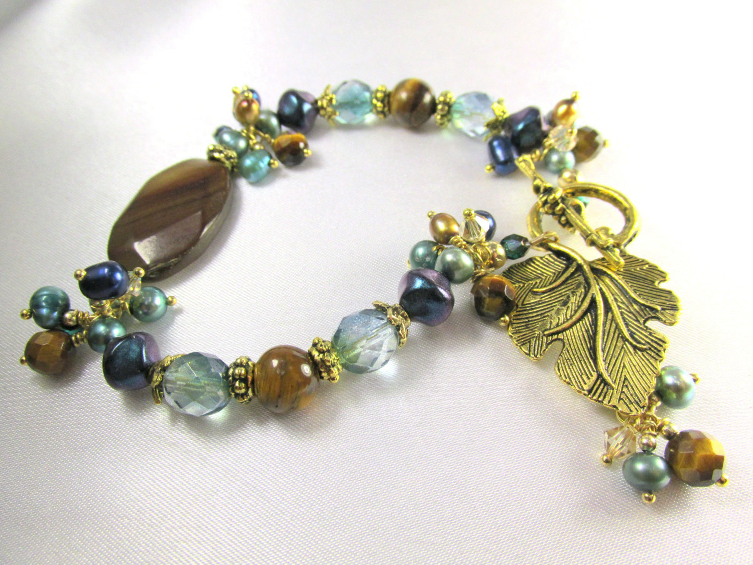 Peacock Freshwater Pearls in Aqua, Teal Blue and Gold with Brown Tigers Eye, Czech glass and gold leaf toggle with charms - Odyssey Creations