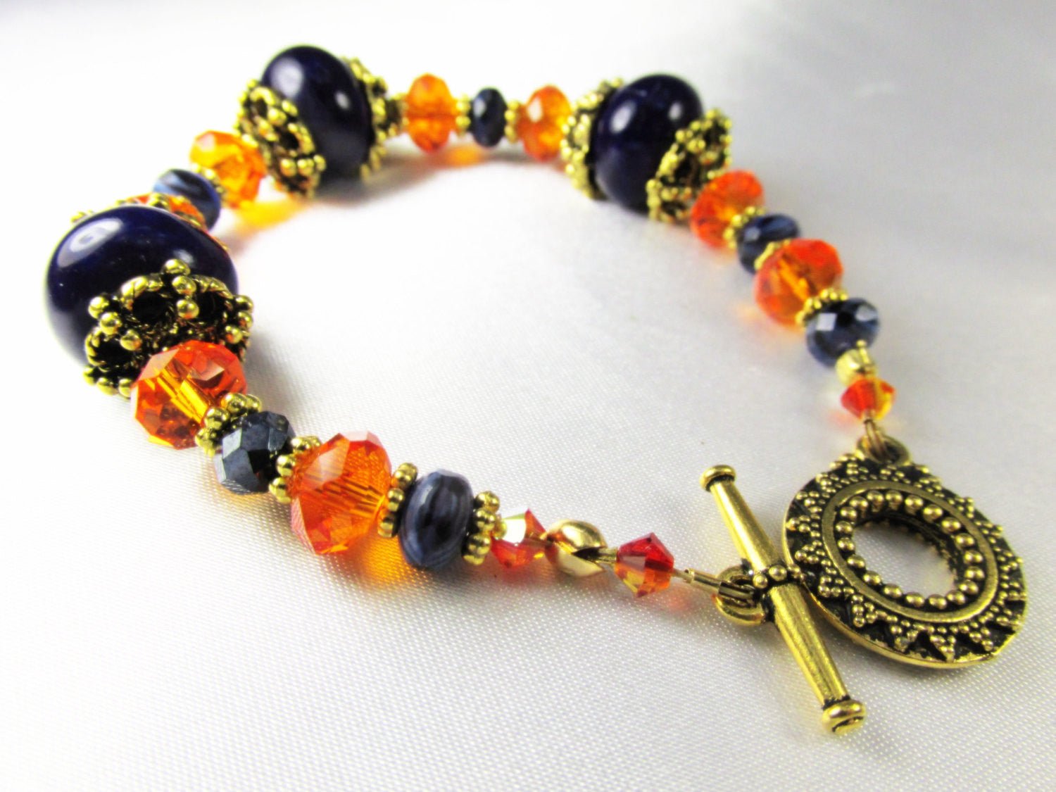 Orange and Blue Bracelet iwith gold sun toggle clasp, faceted dark blue Sodalite semiprecious stones and orange crystals - Odyssey Creations
