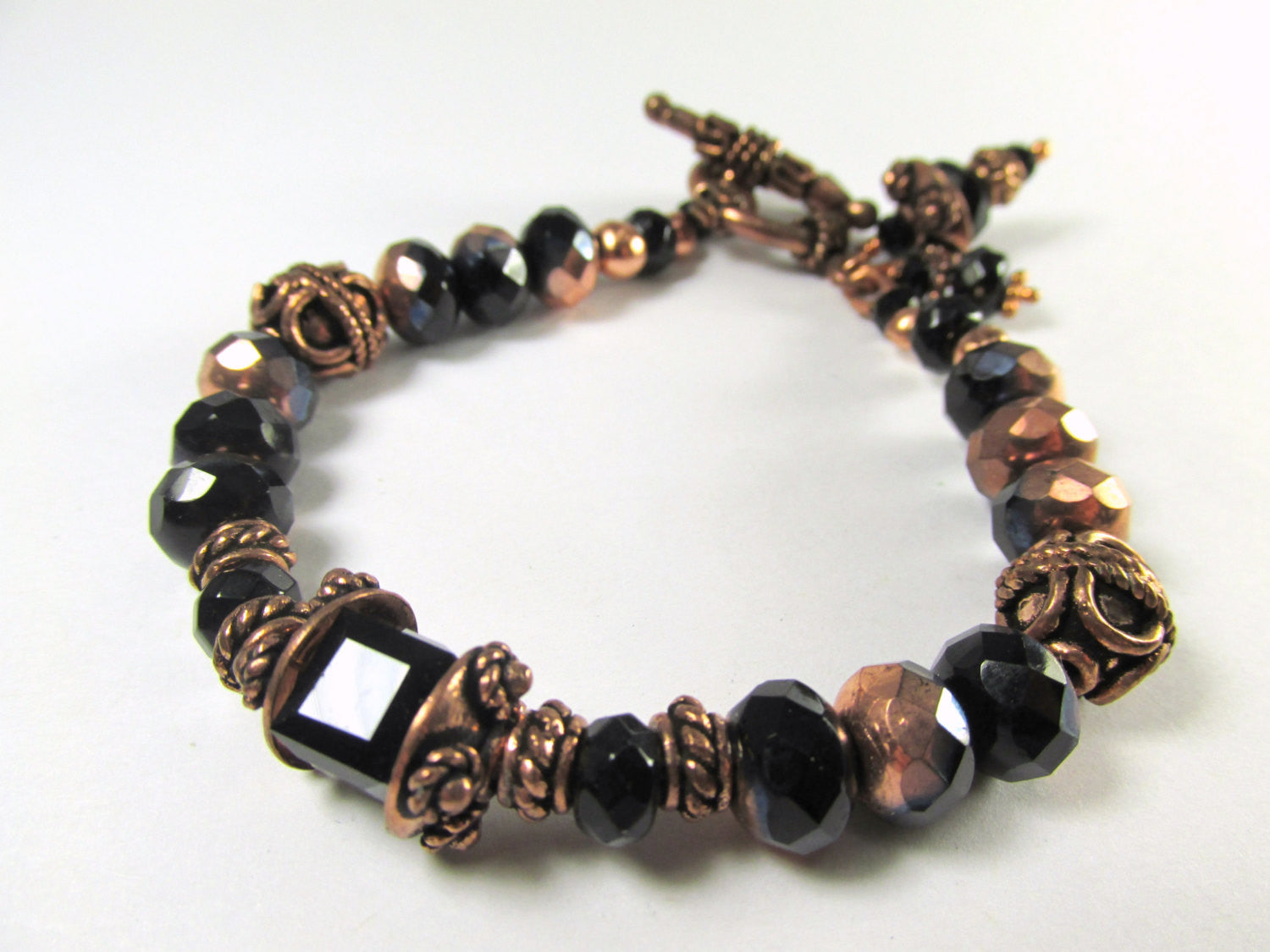 Bracelet in Black and Copper Czech Glass Rondelles Swarovski Cube Center Bead and Bali Style Copper Beads and Toggle Clasp and Charms - Odyssey Creations